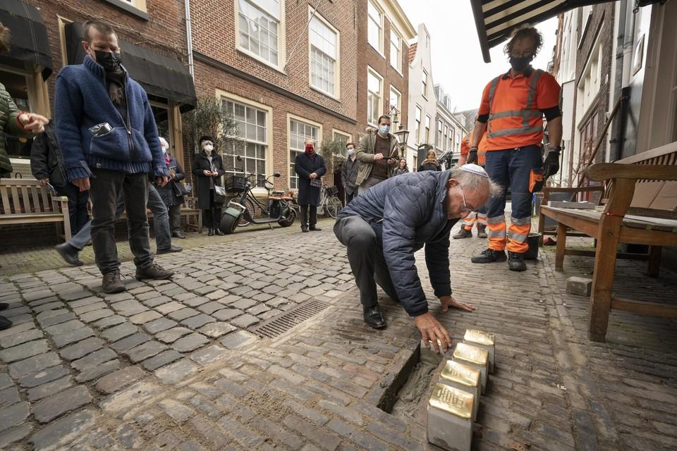 Onder het toeziend oog van Arnold Schalks en stratenmaker Wout Duijndam legt Leo Levie de eerste van de struikelstenen.