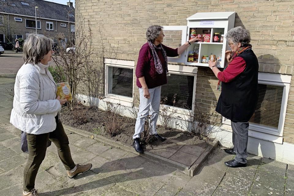 Heleen Feenstra, Marijke van Pernis en Ellis Groothoff (vlnr) vullen het buurtkastje.