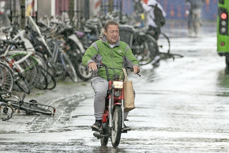 Hans, op zijn rode Tomos. ,,De snelste manier om je te verplaatsen in de stad.''