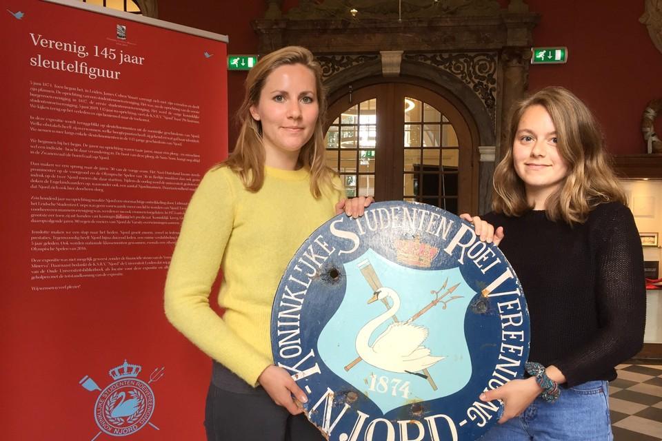 Ellen Breedveld (l) en Emma de Vries met een gevelbord voor het clubgebouw aan de Morsweg.
