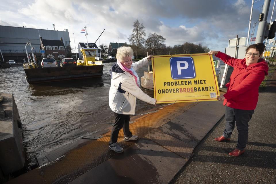 Buitenkagers willen met spandoeken duidelijk maken dat een brug naar Kaageiland hun parkeerprobleem kan oplossen.