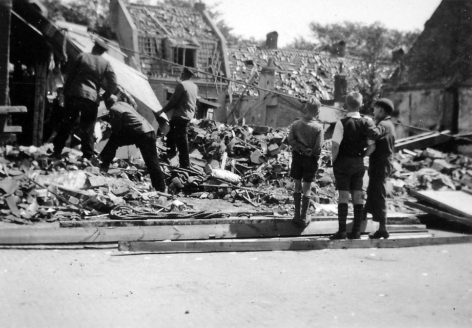 Mannen zoeken tussen de resten van een huis aan de Molenstraat, de nieuwste generatie kijkt toe.