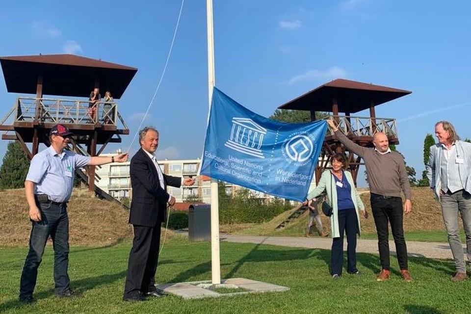 Burgemeester Henri Lenferink houdt de vlag vast samen met provinciebestuurder Willy de Zoete en Boris van der Ham van Unesco Nederland. Tom Hazenberg (rechts) volgt het ritueel.