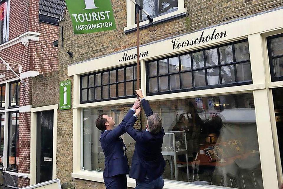 Wethouder Paul de Bruijn en voorzitter Hans Rasch onthullen het VVV-logo bij museum Voorschoten.