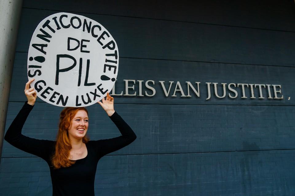 Een demonstrant bij de rechtbank voor aanvang van de bodemprocedure van vrouwenrechtenorganisatie Bureau Clara Wichmann tegen de Staat.