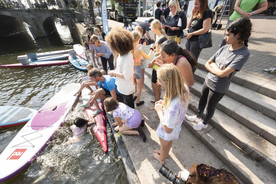 De komst van plastic soup surfer Merijn Tinga leidde tot consternatie op het Stadhuisplein. Twee meisjes vielen in het water, maar stonden snel weer op het droge.