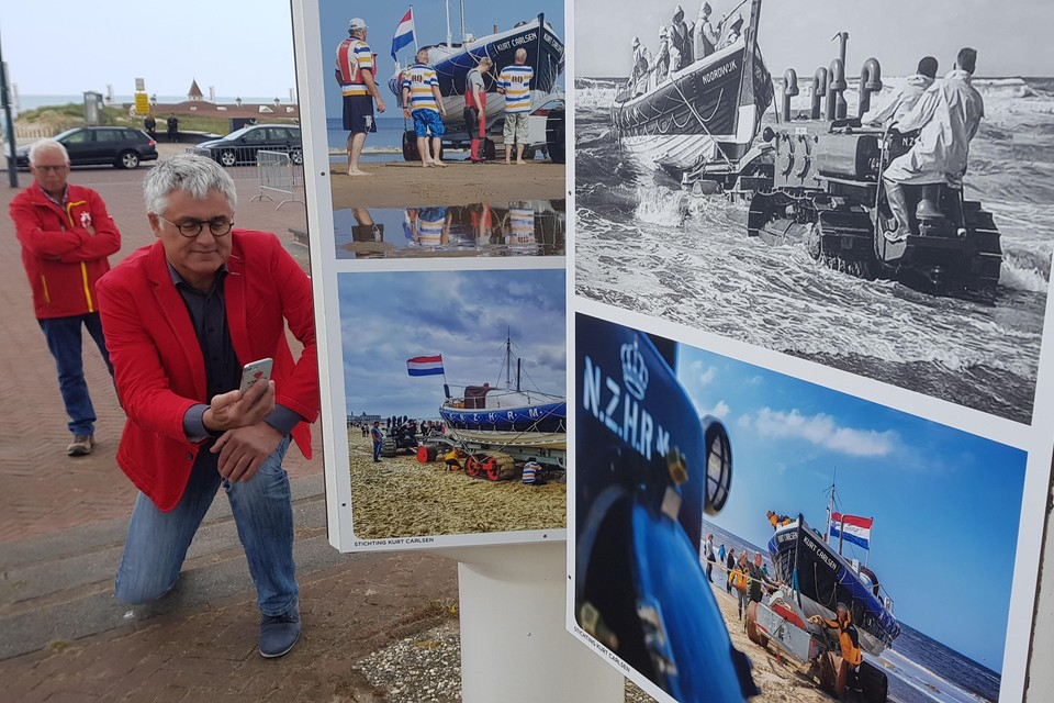 Wethouder Sjaak van den Berg gaat door de knieën om een foto van een van de panelen te maken.