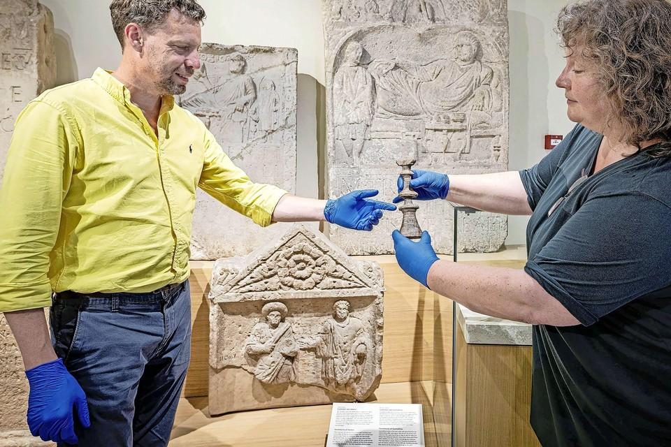 Conservator Jasper de Bruin en onderzoeker Silke Lange tonen een bijzondere meubelpoot.