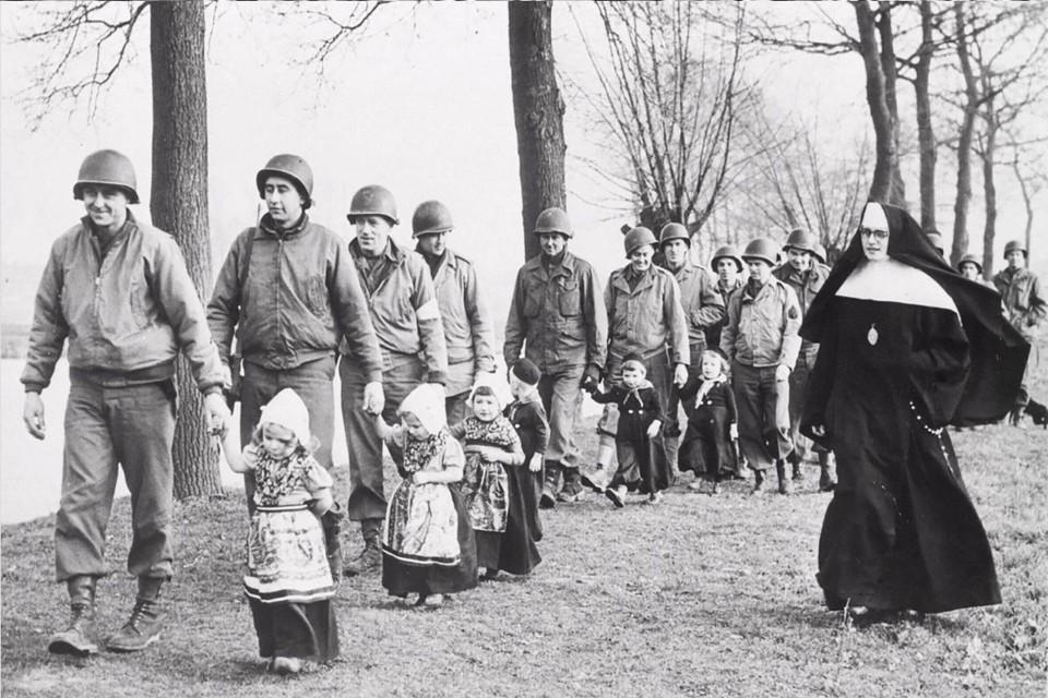 Zuster Marie Pascale aan de wandel met militairen op een uitje met 'Volendammer' kinderen op een foto uit 'Militaire ooggetuigen'.