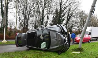 Auto op de zijkant tot stilstand bij botsing in Leiden; lantaarnpaal omvergereden