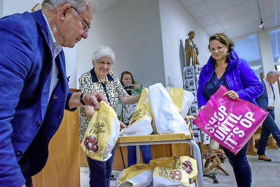 Voorzitter Cees Bijloos van het comité Paardenmarkt en burgemeester Nadine Stemerdink laden de serveerkar vol met oliebollen.
