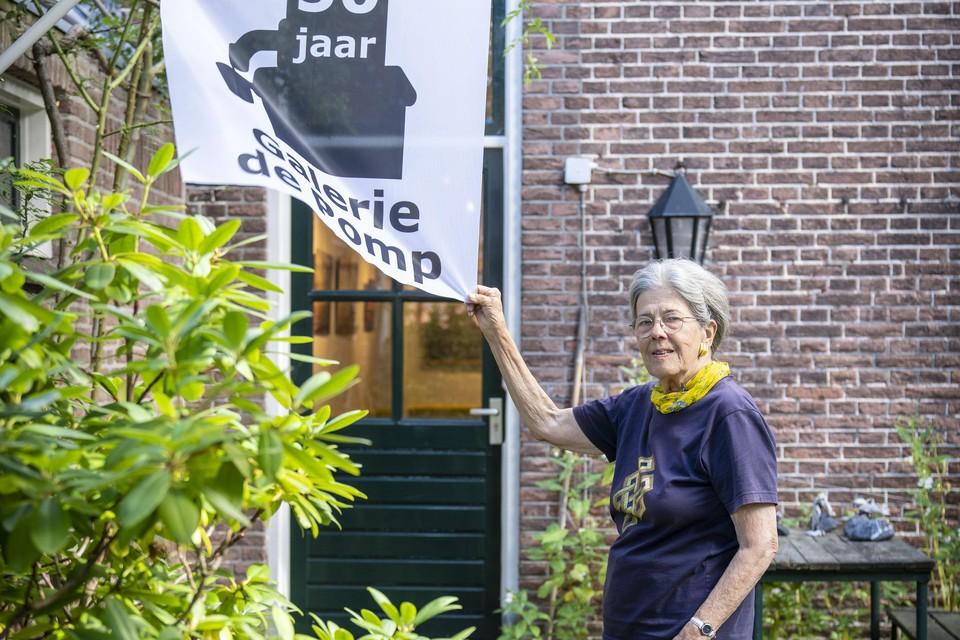 Clara Sikking bij de jubileumvlag van de galerie.