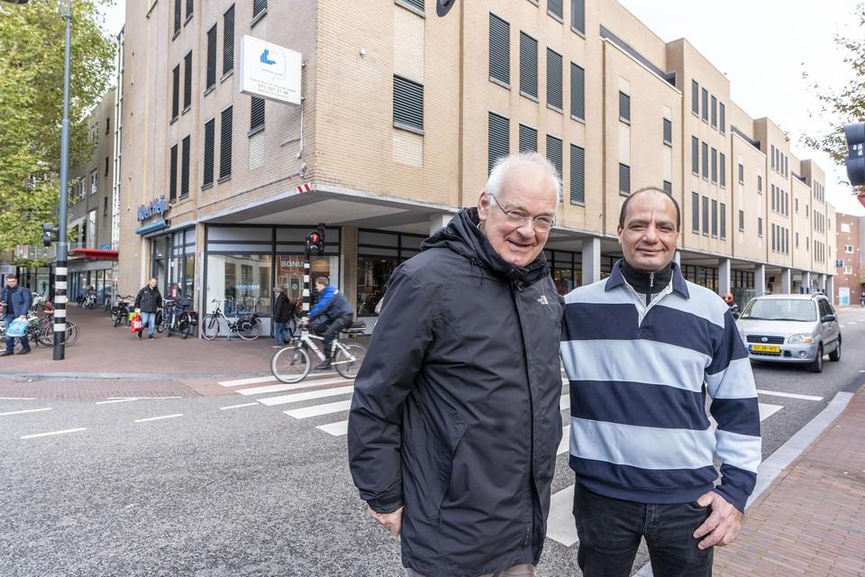 Gepensioneerd dominee Piet Warmenhoven (links) en straatkrantenverkoper 'George' Montesir voor dienss vaste stek bij de AH aan de Hooigracht.