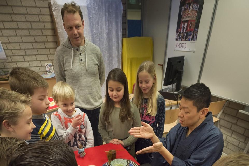Theemeester Takahide Suzuki zet matcha-thee voor de kinderen. Ronald Hilhorst kijkt toe.